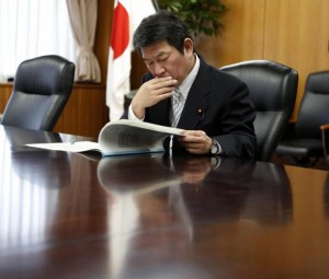 Japan's Economy, Trade and Industry Minister Motegi reads IAEA review report on TEPCO's tsunami-crippled Fukushima Daiichi nuclear power plant after he received it from Lentijo, head of review mission from IAEA in Tokyo